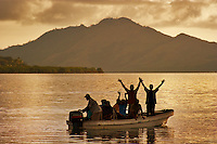 Fijian people travelling in a small boat & waving of the coast of Vanua Levu, Fiji.