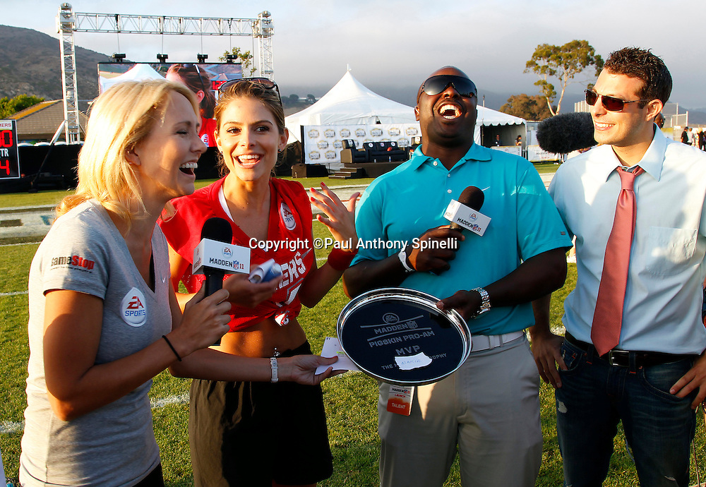Actress Maria Menounos (12) of the Gamers team celebrates winning the Most Valuable Player Award from former St. Louis Rams running back Marshall Faulk (2nd from right) after playing flag football in the EA Sports Madden NFL 11 Launch celebrity and NFL player flag football game held at Malibu Bluffs State Park on July 22, 2010 in Malibu, California. (©Paul Anthony Spinelli)