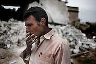 SYRIA, Idlib province: Nizar smokes a cigarette in front of his destroied house by Al Assad forces, on April 11, 2012. He as been alleged to take part to anti-regime demonstrations. ALESSIO ROMENZI