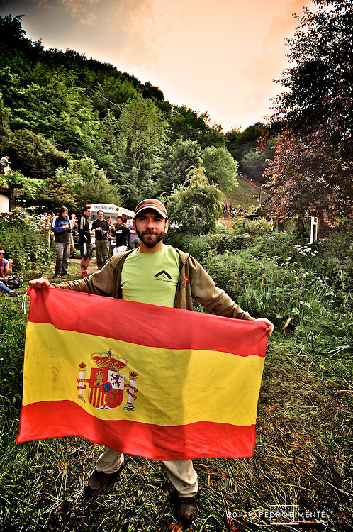 Traditionally organised by and for the people who of the local village of Brockworth, this event is now internationally sought after by people from all around the world. HEre, Pedro Moreno Moreno proudly displaying his spanish national flag..Gloucestershire Cheese Rolling festival. Cooper's Hill, UK.