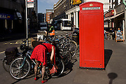 A lady wearing a red dress with black polka dots locks her bike near a red public telephone kiosk.