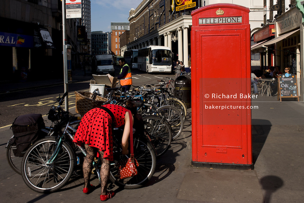 A lady wearing a red dress with black polka dots locks her bike near a red public telephone kiosk.