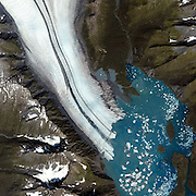 Sep 22, 2009 - USA - Glaciers stay intact as long as the ice thickness and water depth allow them to stay firmly attached to the ground. But when the ice becomes too thin or the water gets too deep, the tip of a glacier starts to float and rapidly cracks into icebergs, creating whatís called a ìcalving edge.î This photograph, captured by NASAís Terra satellite in 2003, shows the calving edge of the Helheim Glacier in Greenland. Comparing similar images from 2001 and 2005 reveals that the solid portion of the glacier has been shrinking rapidly. Measurements from NASA reveal that in just four years, the glacierís margin retreated 4.7 miles and its flow speed increased from 5 to 7.5 miles per year. Between 2001 and 2003, the thickness of the glacier also shrunk by about 131 feet. Unfortunately, the entire Greenland Ice Sheet has been undergoing similar shrinkage, thinning by tens of yards in the past decade. While warmer temperatures have certainly caused some of the thinning, scientists also think that the retreat of the ice margin has played a role: With less grounded ice to slow the ice sheet down, itís moving out to sea at a faster rate.<br /> Retreat Of The Helheim Glacier, Greenland<br /> <br /> ©Exclusivepix