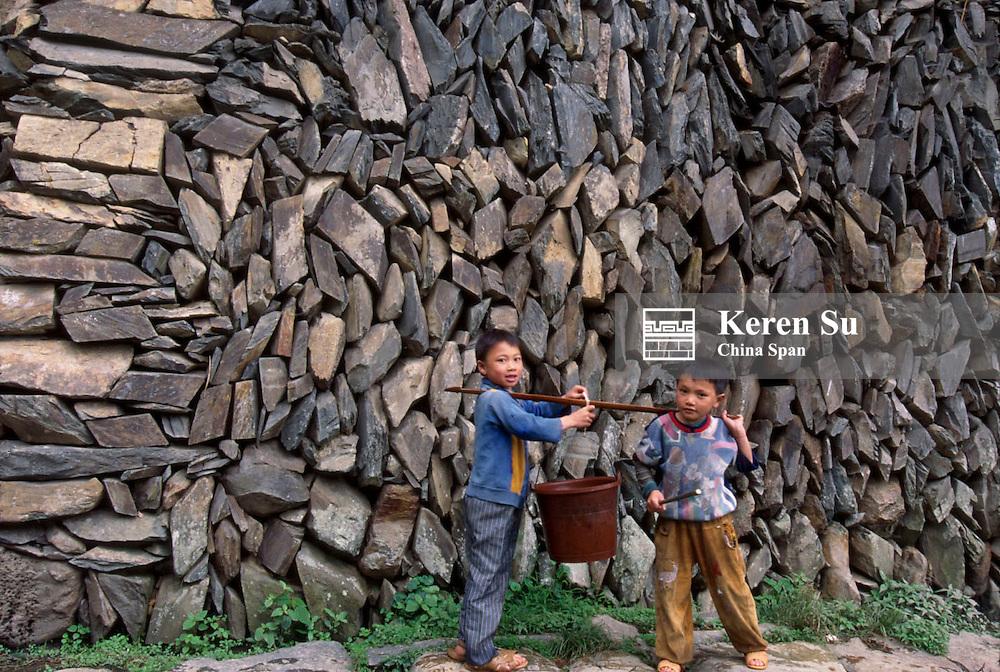 Two boys carrying a water bucket, Longsheng, Guangxi Province, China