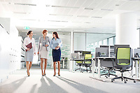 Full-length of businesswomen with file folders walking in office