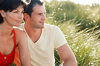 Couple Sitting in tall grass looking out at view portrait