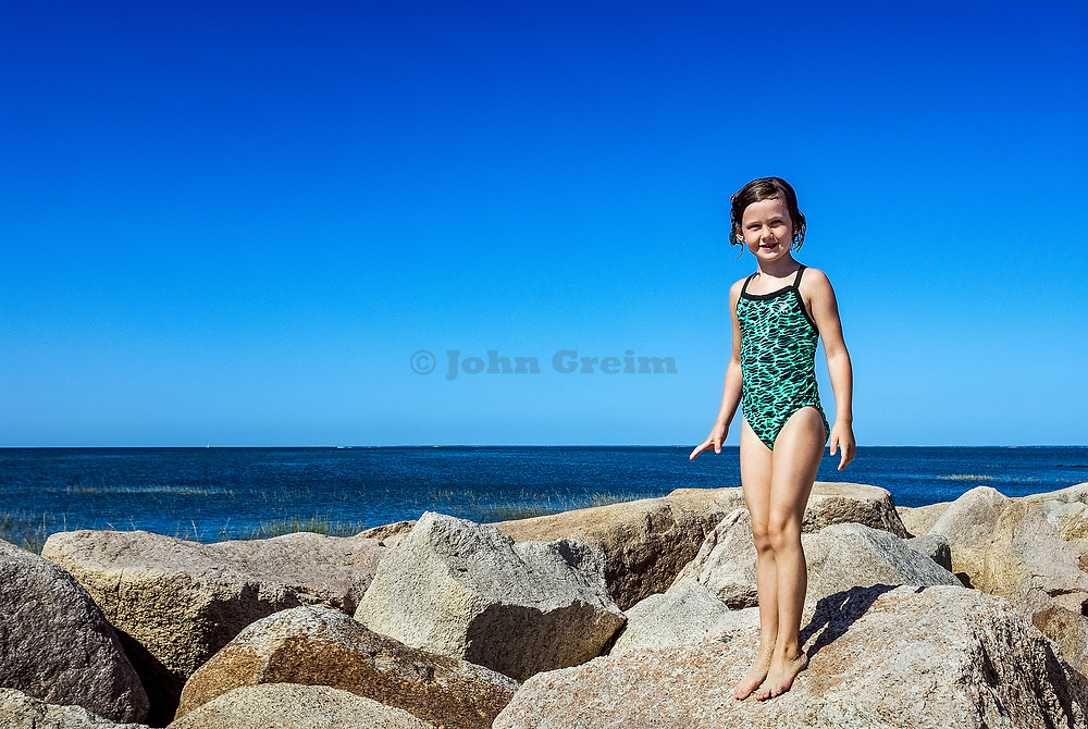 Seven year old girl posing at the beach.