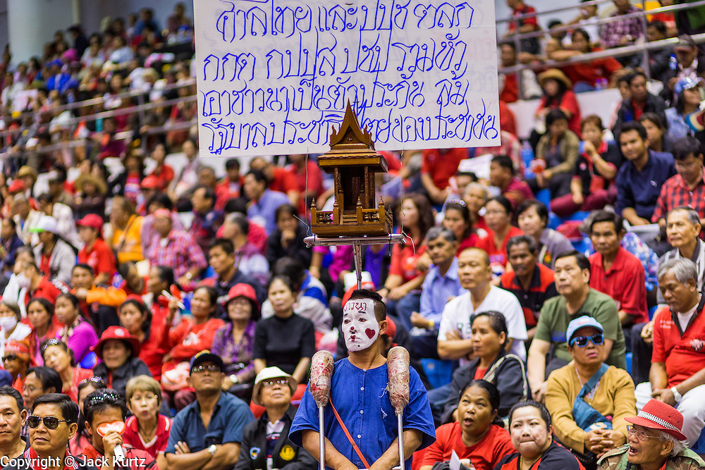 "23 FEBRUARY 2014 - NAKHON RATCHASIMA (KORAT), NAKHON RATCHASIMA, THAILAND:  A Red Shirt supporter walks through the Red Shirt meeting in Korat. The United front of Democracy against Dictator (UDD or Red Shirts), which supports the elected government of Yingluck Shinawatra, staged the ""UDD's Sounding of the Battle Drums"" rally in Nakhon Ratchasima (Korat) to counter the anti-government protests that have gripped Bangkok since November. Around 4,000 of UDD's regional and provincial coordinators along with the organization's core members met at Liptapunlop Hall inside His Majesty the King's 80th Birthday Anniversary Sports Complex in Korat to discuss the organization's objectives and tactics against anti-government protestors, which the UDD says ""seek to destroy the country's democracy."" The UDD leadersa announced that they will march to Bangkok and demonstrate against anti-government protests led by Suthep Thaugsuban.  PHOTO BY JACK KURTZ"