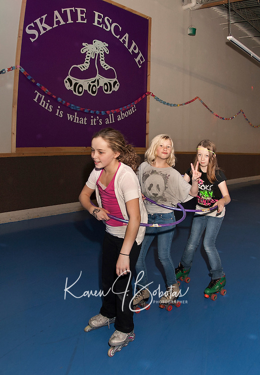 """""""Attached at the hip"""" Gabrielle Isabelle, Maeghan Ash and Kellie Worster participate in the 24 hour Skate a Thon at Skate Escape to benefit the WLNH Children's Auction.   (Karen Bobotas/for the Laconia Daily Sun)"""