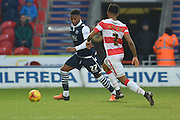 Mahlon Romeo of Millwall FC presses forward under attack from Cedric Evina  of Doncaster Rovers   during the Sky Bet League 1 match between Doncaster Rovers and Millwall at the Keepmoat Stadium, Doncaster, England on 27 February 2016. Photo by Ian Lyall.