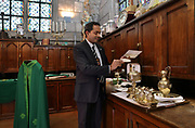 Patrick Kollannur, sacristan, preparing the objects to be used during mass, in the main room of the sacristy at the Cathedrale Notre-Dame de Paris, or Notre-Dame cathedral, built 1163-1345 in French Gothic style, on the Ile de la Cite in the 4th arrondissement of Paris, France. In this room, preparations are made for services and mass, and books and robes are stored. Picture by Manuel Cohen