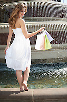 Portrait of a young woman standing by fountain carrying shopping bags