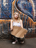 Young woman squatting by brick wall pretending begging