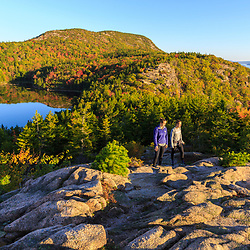 """Two women hiking on """"The Beehive"""" in fall in Maine's Acadia National Park.`"""