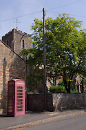 Photo by Andrew Tobin/Tobinators Ltd - 07710 761829 - A red telephone box outside St Martin's church in Witcham during the World Peashooting Championships held at Witcham, Cambridgeshire, UK on 13th July 2013. Run in conjunction with the village fair, the Championships have been held in Witcham since 1971 when they were started by a Mr Tyson, the village schoolmaster, in order to raise funds for the village hall.Competitors come from as far afield as the USA and New Zealand to attempt to win the event. The latest technology is often used, including laser sights and titanium and carbon fibre peashooters. All peashooters must conform to strict length rules, not exceeding 12 inches, and have to hit a target 12 feet away. Shooting 5 peas at a plasticine target attached to a hay bale, the highest scorers move through the initial rounds to a knockout competition, followed by a sudden death 10-pea shootout.