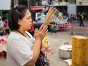 "07 AUGUST 2014 - BANGKOK, THAILAND:  A woman prays at Pek Leng Keng Mangkorn Khiew Shrine. Thousands of people lined up for food distribution at the Pek Leng Keng Mangkorn Khiew Shrine in the Khlong Toei section of Bangkok Thursday. Khlong Toei is one of the poorest sections of Bangkok. The seventh month of the Chinese Lunar calendar is called ""Ghost Month"" during which ghosts and spirits, including those of the deceased ancestors, come out from the lower realm. It is common for Chinese people to make merit during the month by burning ""hell money"" and presenting food to the ghosts. At Chinese temples in Thailand, it is also customary to give food to the poorer people in the community.     PHOTO BY JACK KURTZ"