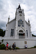 View of St. Ann's Church from Main Street view with tourists, Mackinac Island, Michigan, USA.