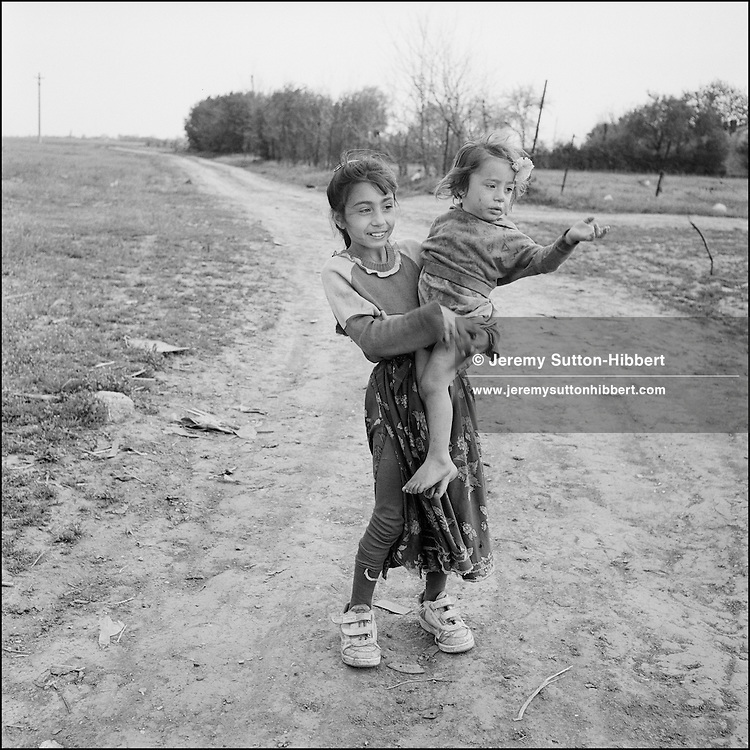 Zena Stanescu and her sibling in the Kalderash Roma camp of Sintesti, near Bucharest. Zena does not attend school, instead she stays in the camp to help her parents with chores and to look after her siblings. August 1994