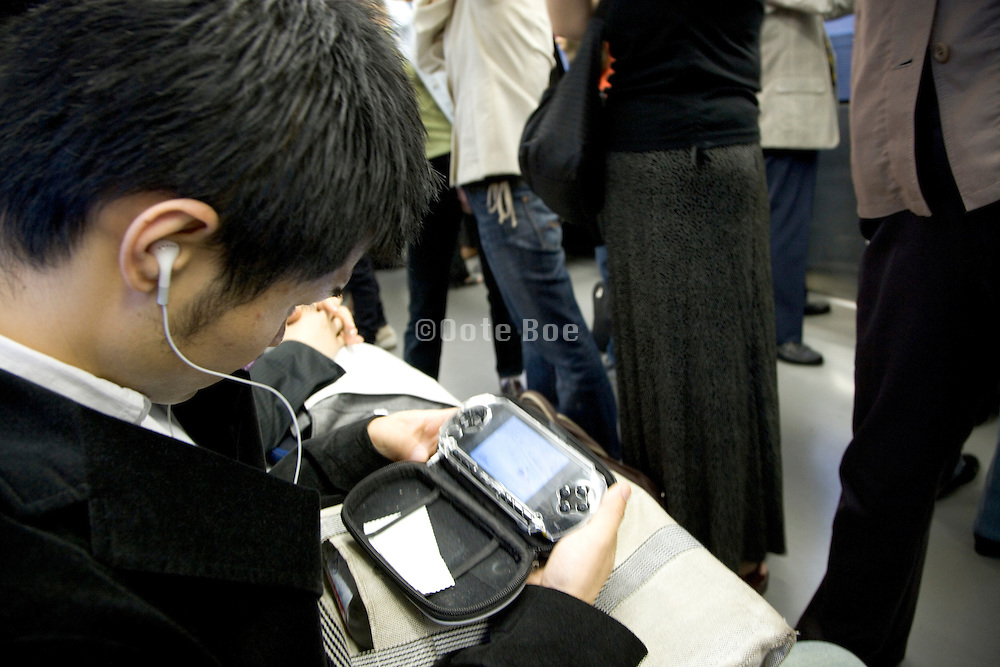 young Japanese man watching a movie on his sony play station while commuting to work