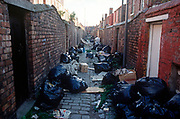"During the Liverpool binmens' strike of 1991, litter and refuse bags collect in the back alleyway of back-to-back terraced houses, on 14th June 1991, in Liverpool, England. Surrounded by black bin-bags during the Merseyside dustmans' strike of 1991, two young ""Scouse' girls lean against a brick wall in a rear alleyway between poor terraced housing in Liverpool, England. The industrial action against the local authority was a health problem for Liverpool over that summer when streets filled with rubbish. Vermin like rats ran around and public city parks filled with every kind of refuse and garbage. Few of these back-to-backs existed in the 1990s after being cleared to allow construction of high-rise tower-blocks and flats. (Photo by Richard Baker / In Pictures via Getty Images)"