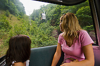 Mother and daughter ride an aerial tram.