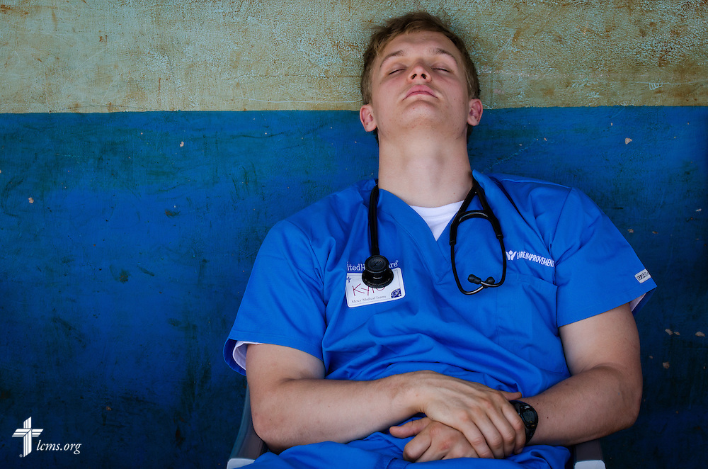 Kyle Uhlig, a student from Pittsburgh, Pa., attending First Trinity and First Lutheran churches, takes a short nap during downtime at the Mercy Medical Team clinic Thursday, June 12, 2014, at the Luanda Doho Primary School in Kakmega County, Kenya. LCMS Communications/Erik M. Lunsford