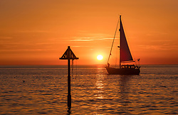 © Licensed to London News Pictures. 28/06/2018. Aberystwyth, UK. A yacht sails through a  spectacular sunset over Cardigan Bay , Aberystwyth, at the end of a day of record breaking temperatures across the UK,. Photo credit: Keith Morris/LNP