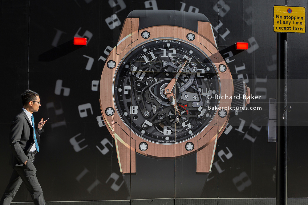 A businessman walks past a construction hoarding of a watch outside the new Richard Mille shop in New Bond Street, on 25th February 2019, in London, England.