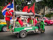 "10 DECEMBER 2012 - BANGKOK, THAILAND:   A Red Shirt ""tuk-tuk"" (three wheeled taxi) goes to the Pheu Thai offices on Petchaburi Road in Bangkok Monday. The Thai government announced on Monday, which is Constitution Day in Thailand, that will speed up its campaign to write a new charter. December 10 marks passage of the first permanent constitution in 1932 and Thailand's transition from an absolute monarchy to a constitutional monarchy. Several thousand ""Red Shirts,"" supporters of ousted and exiled Prime Minister Thaksin Shinawatra, motorcaded through the city, stopping at government offices and the offices of the Pheu Thai ruling party to present demands for a new charter.       PHOTO BY JACK KURTZ"