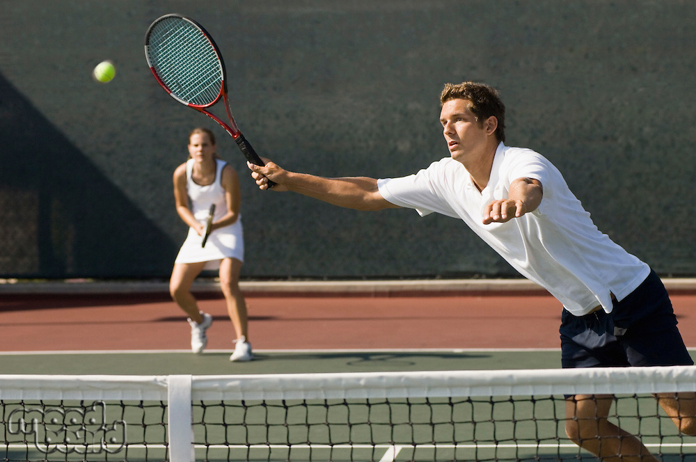 Doubles Player stretching Hitting tennis ball with forehand near net