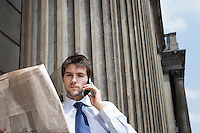 Businessman Reading Newspaper and Talking on Cell  Phone outside building