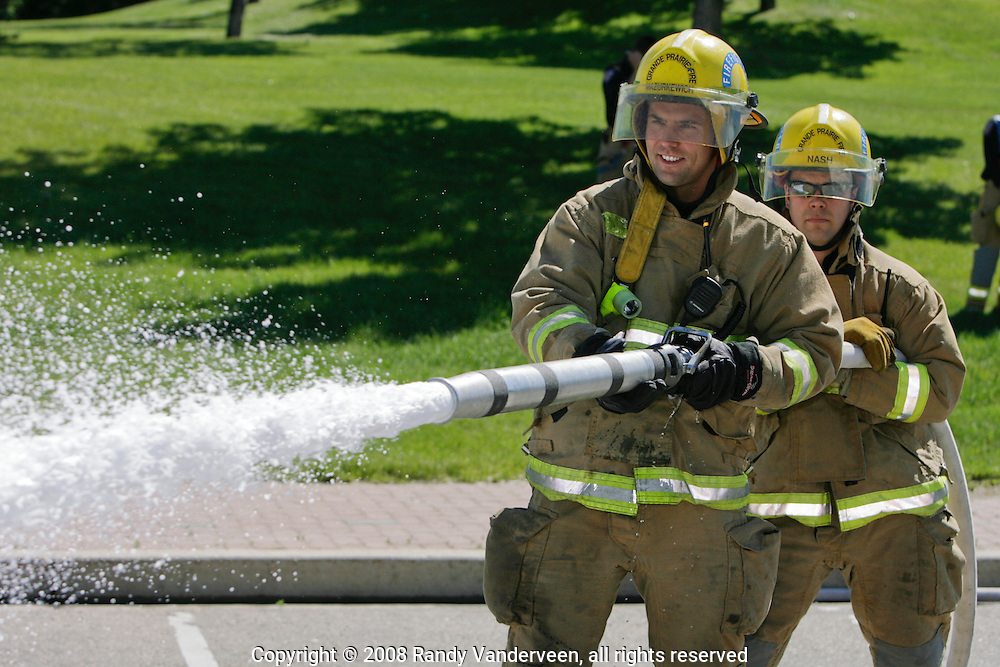 © 2008 Randy Vanderveen, all rights reserved.Grande Prairie, Alberta.Firefighters Jason Mazurkewich and Ryan Nash lay down some foam as Grande Prairie firefighters train in Muskoseepi Park by conducting some Performance Standard Drills during the mid-day hours of a summer day.