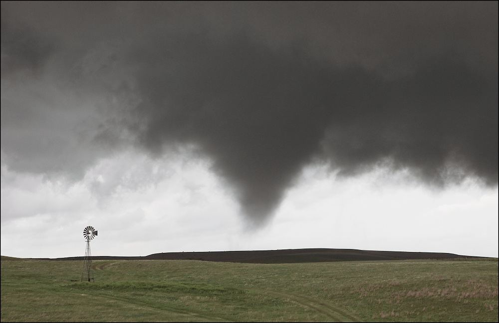 Isolated supercell produced a tornado in a farm field in Lincoln, Kansas next to an old windmill.