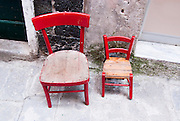 Two red chairs sit along the narrow sidewalk in Vernazza, Italy.