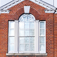 Venetian Window with rubbed brick voussoirs and fluted keystone. truncated pediment in Lavenham, Suffolk, UK.