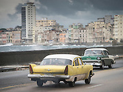 Most classic cars have been converted to diesel since the cost of gas is so high, contributing to warn patina over the once colorful buildings on this stormy day in Havana.