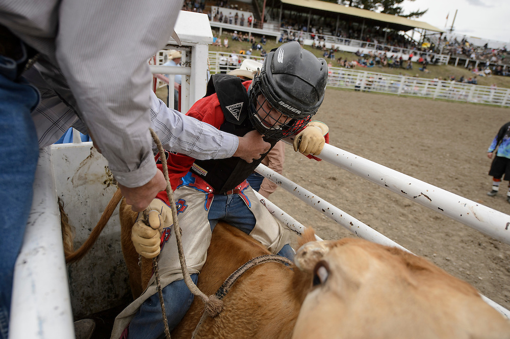 A young cowboy competing in the bull riding competition at the Falkland Stampede.
