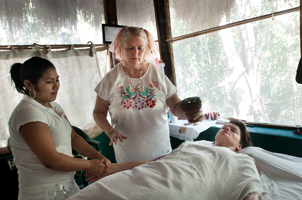 Owner of the Jungle Spa, Sandra Dayton, cleaninsing the aura of one of her guests with incense, as a mayan woman gives massage...The Jungle Spa in Puerto Morelos, Mexico, just 20 minutes from Cancun is managed by Sandra Dayton who is also the co-founder of the non-profit organization Lu'um K'aa Nab that helps mayan women make a living for them selves by selling handicraft and giving mayan massage at the Jungle Spa.