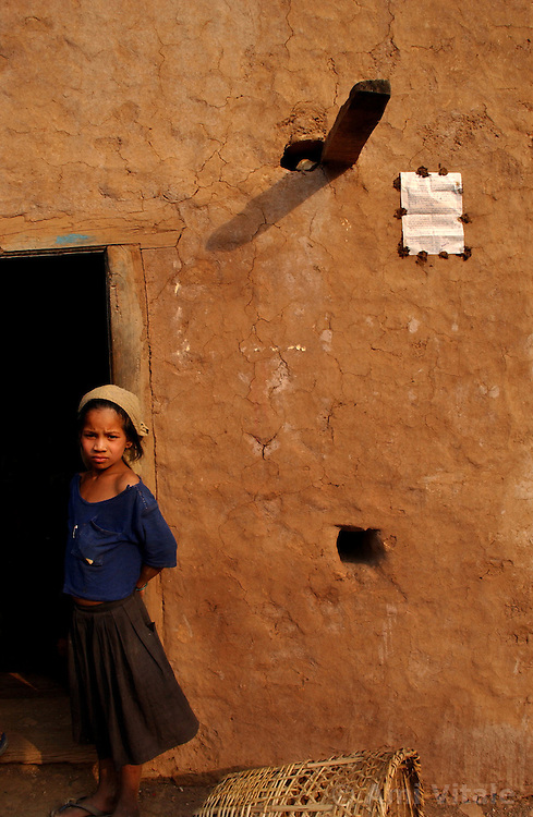 """RUKUM DISTRICT, NEPAL, APRIL 17, 2004: A Nepalese child stands next to a wall where a notice is put up with dung announcing the release of kidnapped prisoners in Rukum District April 17, 2004. Maoists regularly kidnap people for cultural programs where they are educated about the movement.  Analysts and diplomats estimate there about 15,000-20,000 hard-core Maoist fighters, including many women, backed by 50,000 """"militia"""".  In their remote strongholds, they collect taxes and have set up civil administrations, and people's courts. They also raise money by taxing villagers and foreign trekkers.  They are tough in Nepal's rugged terrain, full of thick forests and deep ravines and the 150,000 government soldiers are not enough to combat this growing movement that models itself after the Shining Path of Peru. (Ami Vitale/Getty Images)"""