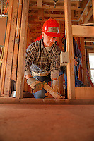 University Scholars' director Sean Cassidy caulks while working on the Build-A-Block Habitat for Humanity project.