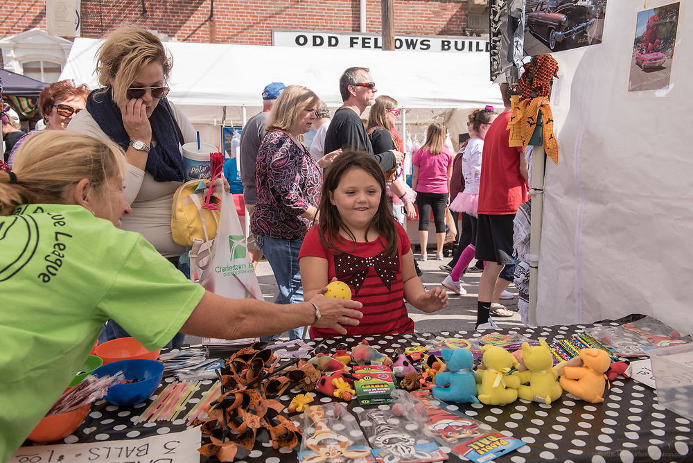 Jo Peers, left, in the Floyd County Animal Rescue League booth, gives Ryan Allen, 6, of Georgetown another ball to throw as her mother, Ann Allen, waits at the 2015 Hot Rod harvest Homecoming in New Albany, Ind. Oct. 10, 2015