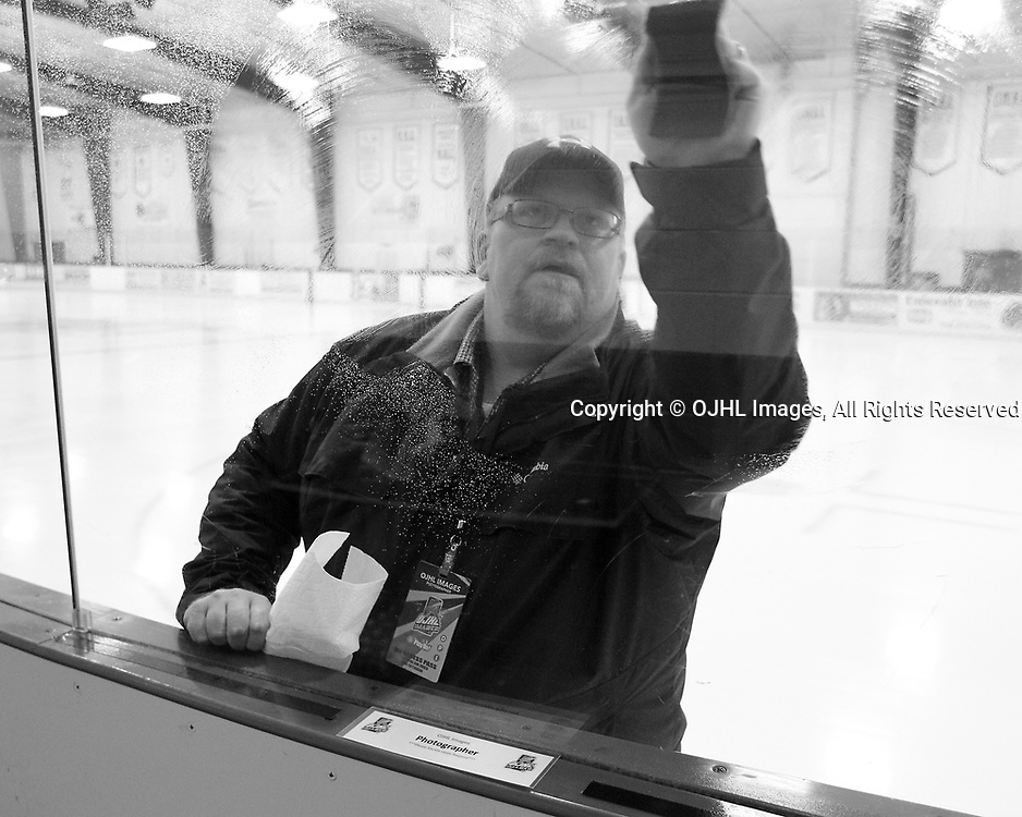 GEORGETOWN, ON  - APR 18,  2017: Ontario Junior Hockey League, Championship Series. Georgetown Raiders vs the Trenton Golden Hawks in Game 3 of the Buckland Cup Final. Photographer Shawn Muir cleans the glass prior to game.<br /> (Photo by Tim Bates / OJHL Images)
