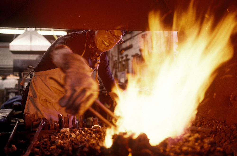 Canada, Nova Scotia, Lunenburg, Laurie Fisher Huck works as blacksmith at Lunenburg Forge on autumn afternoon