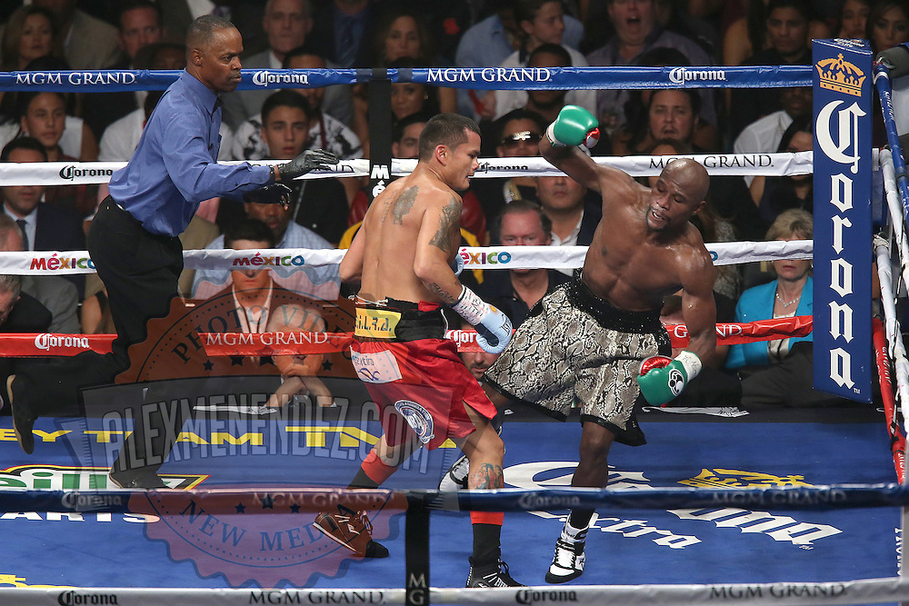 LAS VEGAS, NV - SEPTEMBER 13: - (L-R) Floyd Mayweather Jr. falls back after a punch by Marcos Maidana during their WBC/WBA welterweight title fight at the MGM Grand Garden Arena on September 13, 2014 in Las Vegas, Nevada. (Photo by Alex Menendez/Getty Images) *** Local Caption *** Floyd Mayweather Jr; Marcos Maidana