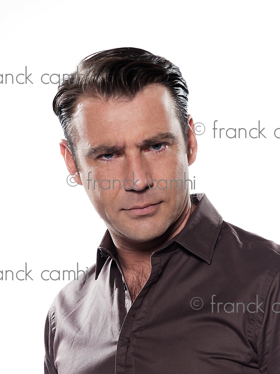 Handsome caucasian man serious portrait on white isolated background with brown shirt