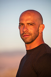 portrait of a rugged bald man outdoors at sunset