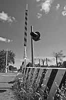 barriere alzate nei pressi di uno dei tanti passsaggi a  livello che attraversano anche stradine di campagna nel Salento. Reportage che racconta le situazioni che si incontrano durante un viaggio lungo le linee ferroviarie SUD EST nel salento.