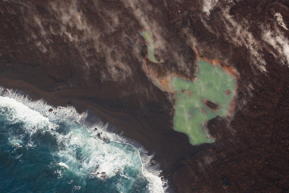 Kilauea's east rift zone overflight: A green pond sits just inland of the new beach that has been formed at Kapoho.
