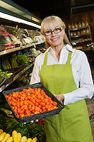 Portrait of senior market employee holding vegetables