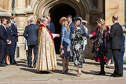 Windsor, UK. 21st April 2019. Princess Beatrice shakes the hand of the Dean of Windsor, the Rt Revd David Conner KCVO, as she arrives to attend the Easter Sunday service at St George's Chapel in Windsor Castle.